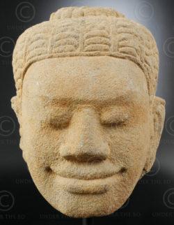 Tête khmere antique KM83E. Tête en grès jaune d'une divinité hindoue souriante.